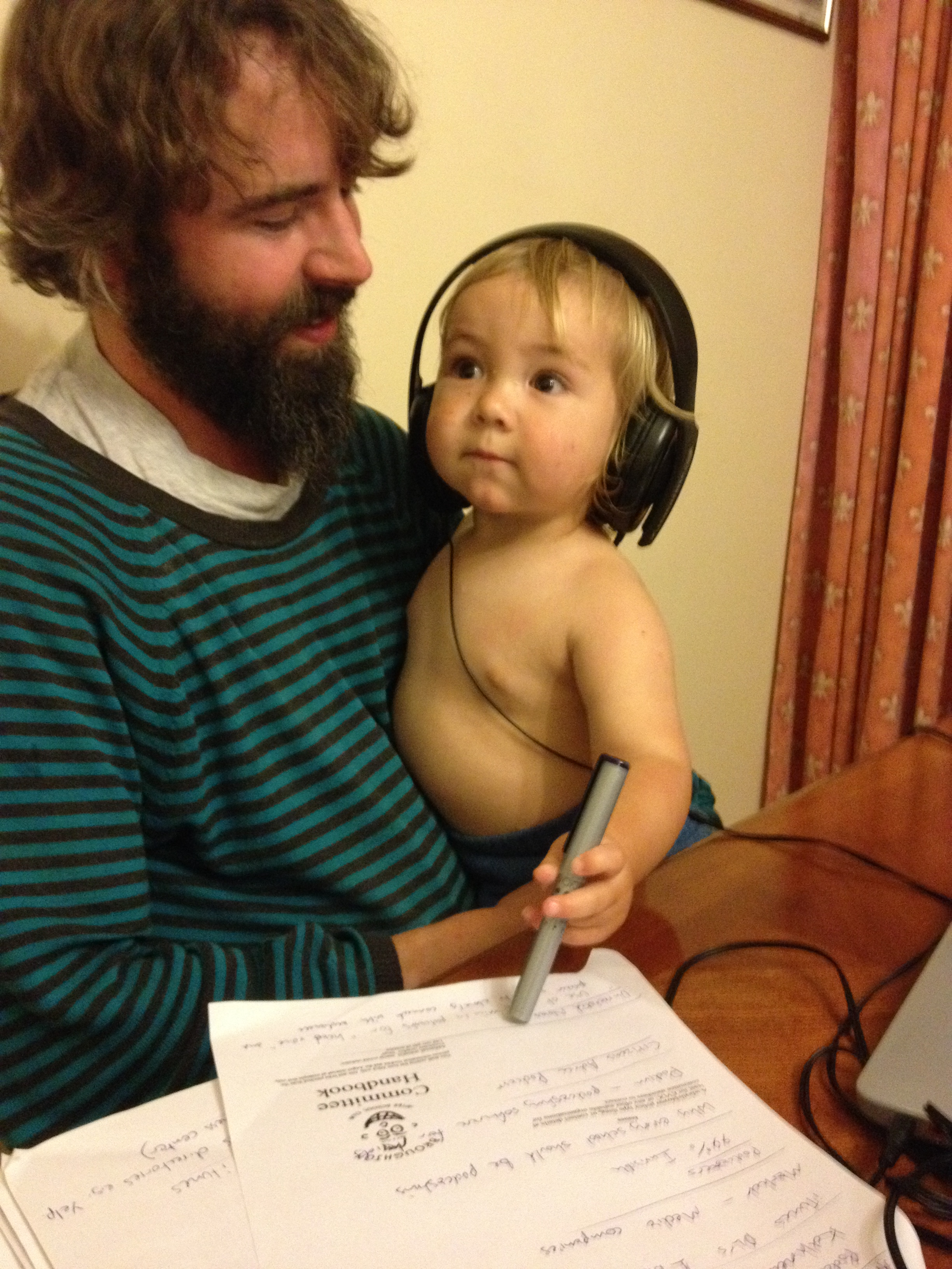 Ross and his baby, the baby is wearing headphones with a look of deep concentration whilst holding a pen over a pad of paper.